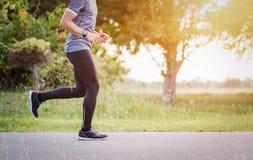 Молодой человек бежит на заходе солнца дороги Стоковое фото RF