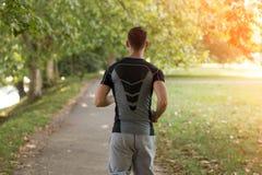 Молодой человек бежит на дороге - назад освещенном заходе солнца Стоковое Изображение
