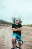 Молодой человек битника на велосипеде стоковая фотография