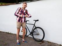 Молодой человек битника стоя около его велосипеда Стоковое Изображение