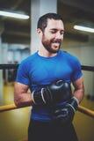 Молодой человек бокса с перчатками бокса усмехаясь на кольце Кавказский спортсмен в черных перчатках prepairing для kickboxing тр Стоковая Фотография