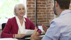Молодой человек более старой коммерсантки интервьюируя в офисе сток-видео