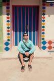 Молодой человек брюнет, нося в голубой рубашке, сандалии, солнечные очки, с сумкой Стоковое Фото