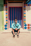Молодой человек брюнет, нося в голубой рубашке, сандалии, солнечные очки, с сумкой Стоковая Фотография
