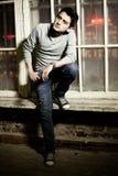 Молодой человек брюнет сидя на деревянном поле стоковые фотографии rf