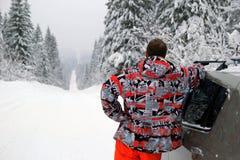 Молодой человек близко к автомобилю на дороге зимы с снегом покрыл ели Стоковые Фото