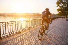 Молодой человек велосипед задействуя дороги в вечере Стоковое Фото