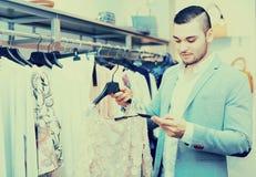 Молодой человек выбирая одежды для девушки Стоковое Фото