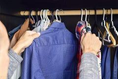 Молодой человек выбирая рубашку от одежды кладет на полку стоковое фото