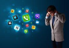 Молодой человек вызывая телефоном с различными иконами Стоковые Фото