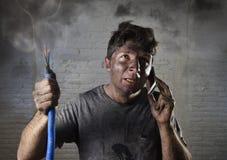 Молодой человек вызывая для помощи после аварии с пакостной, который сгорели стороной в смешном унылом выражении Стоковые Фотографии RF