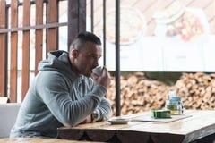 Молодой человек выпивает кофе внешний Стоковая Фотография