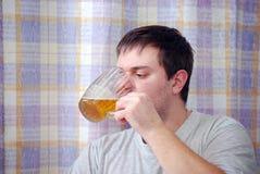 Молодой человек выпивает пиво в кухне Стоковое фото RF
