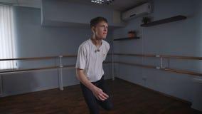 Молодой человек выполняет хмель танца тазобедренный в большом зале Движения танца с его руками Студия танца с поручнями дальше видеоматериал