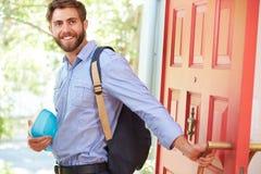 Молодой человек выходя домой для работы с упакованным обедом Стоковое фото RF