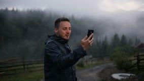 Молодой человек в вечере в горах связывает на skype с друзьями сток-видео