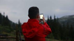Молодой человек в вечере в горах улавливает сигнал сток-видео