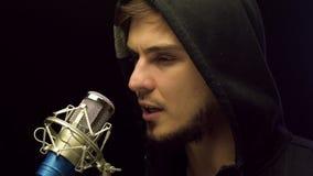 Молодой человек в вскользь standng ткани за микрофоном и речью делать видеоматериал