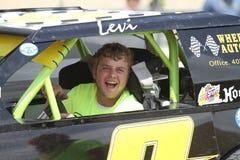 Молодой человек в гоночной машине в параде в маленьком городе Америке Стоковые Фотографии RF