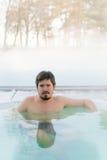 Молодой человек в джакузи ванны outdoors на зиме Стоковое Фото