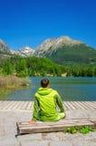 Молодой человек в зеленой куртке ясным озером горы стоковые изображения rf