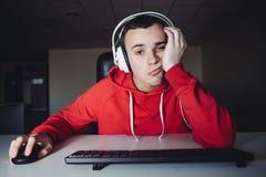 Молодой человек в компьютерах пользы наушников на ноче Gamer играет игры на компьютере стоковые изображения