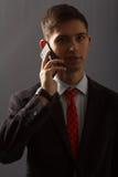 Молодой человек в костюме говорит на телефоне надувательства Стоковые Изображения RF