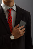 Молодой человек в костюме держа телефон на его комоде Стоковое фото RF