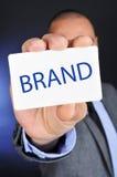 Молодой человек в костюме показывает шильдик с брендом слова стоковые изображения rf