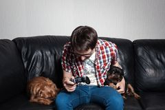 Молодой человек в красной рубашке и голубых джинсах сидит дома и играет видеоигры вместе с их собаками Плохой парень плачет и ang стоковые изображения