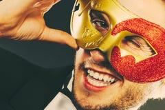 Молодой человек в маске масленицы на темноте Стоковая Фотография