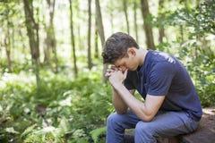 Молодой человек в молитве Стоковые Изображения