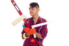 Молодой человек в перчатках держа вровень, крене и правителе Стоковые Фотографии RF