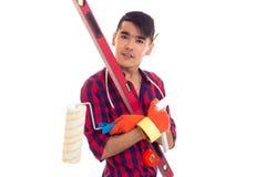 Молодой человек в перчатках держа вровень, крене и правителе Стоковое Изображение RF