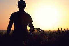Молодой человек в поле около велосипеда Стоковые Фотографии RF