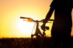 Молодой человек в поле около велосипеда Стоковое Изображение