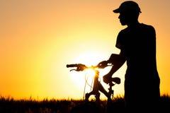Молодой человек в поле около велосипеда Стоковая Фотография