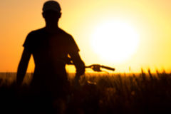 Молодой человек в поле около велосипеда Стоковое Изображение RF