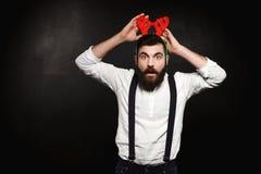 Молодой человек в поддельных рожках оленей представляя над черной предпосылкой стоковые фотографии rf