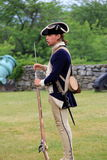 Молодой человек в платье периода, демонстрируя пользу мушкета, форт Ticonderoga, Нью-Йорк, 2014 Стоковые Фотографии RF