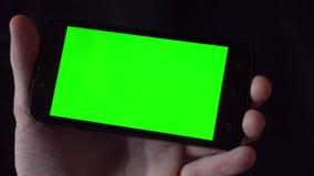 Молодой человек в рубашке держа телефон с зеленым экраном перед им сток-видео