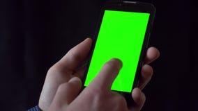 Молодой человек в рубашке держа телефон с зеленым экраном перед им видеоматериал