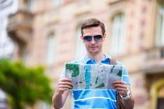 Молодой человек в солнечных очках с картой города и рюкзак в Европе Кавказское туристское смотрящ карту европейского города внутр стоковая фотография rf