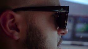 Молодой человек в солнечных очках управляет автомобилем на дороге сток-видео