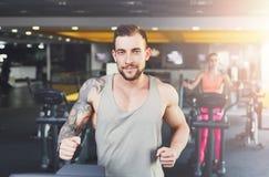 Молодой человек в спортзале, который побежали на третбане Стоковые Изображения