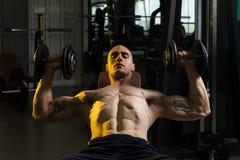 Молодой человек в спортзале работая комод с гантелями Стоковые Изображения