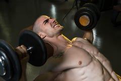 Молодой человек в спортзале работая комод с гантелями Стоковая Фотография RF