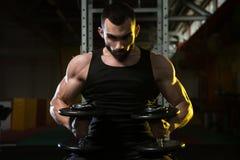 Молодой человек в спортзале работая комод с гантелями Стоковое фото RF