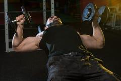 Молодой человек в спортзале работая комод с гантелями Стоковое Фото