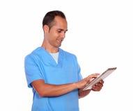 Молодой человек в форме медсестры используя ПК таблетки стоковые фото